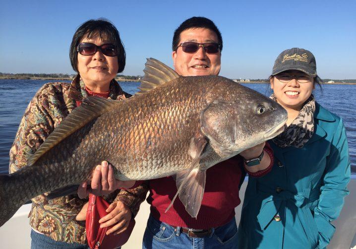 Three happy angers holding a Black Drum fish