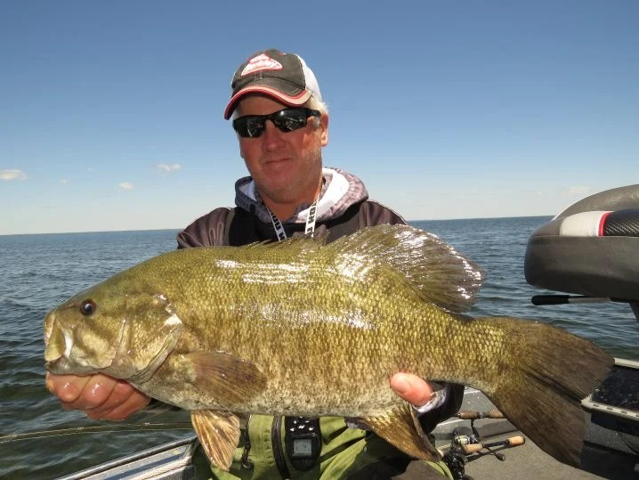 An angler wearing sunglasses and a cap holding a smallmouth bass with open water behind him