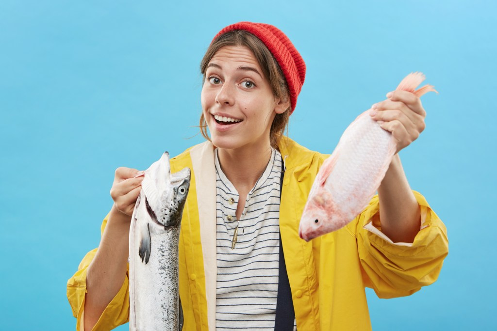 a young woman holding two different fish