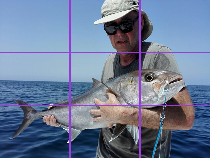 An angler holding a fish. The photo is showing fishing photography tips and how to use the rule of thirds.