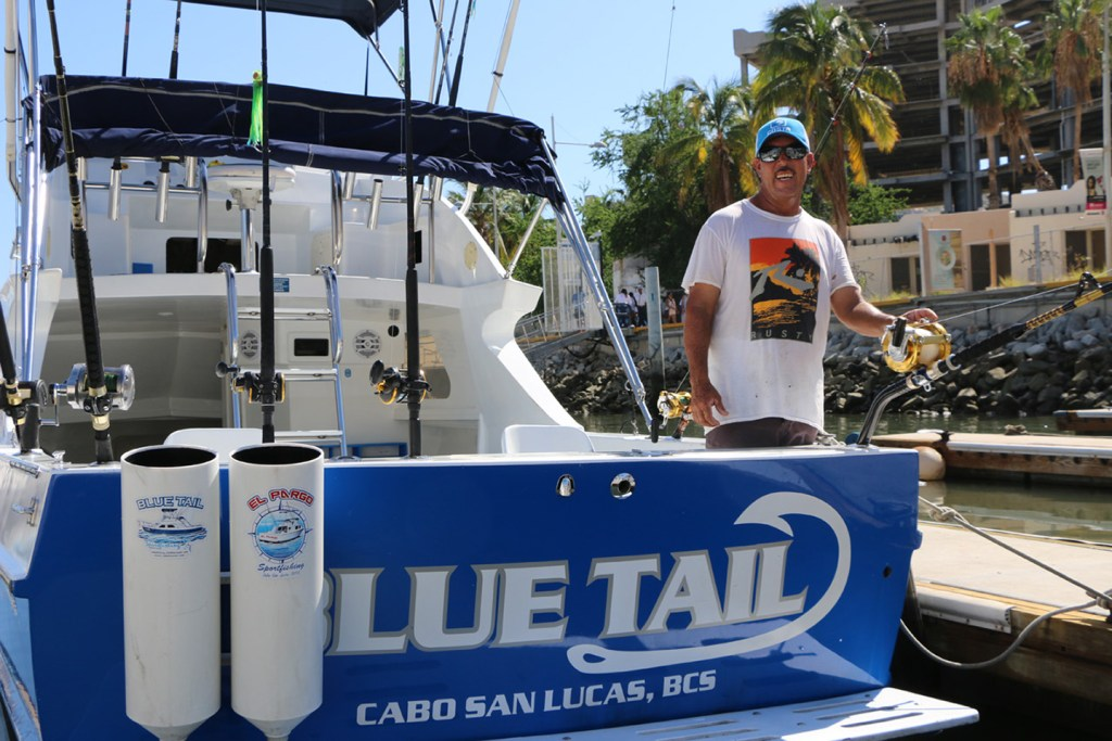 A Mexican charter fishing captain standing at the back of his boat in Cabo San Lucas.