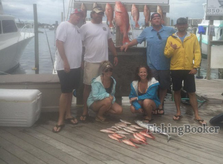 Blurry photo of people and fish caught on their trip standing in the marina with boats in the background