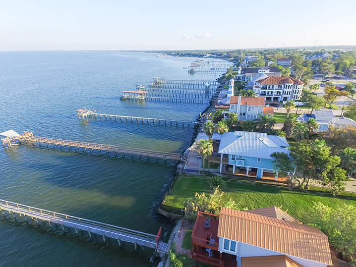 Row of oceanfront houses in Galveston with fishing piers.