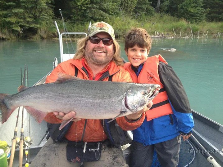A young boy and his dad on a family fishing trip in Kenai, Alaska holding Chinook Salmon.