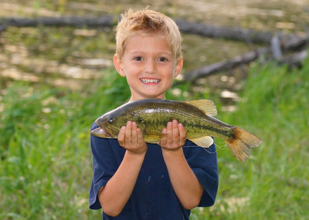 a young smiling boy holding a fish he just caught