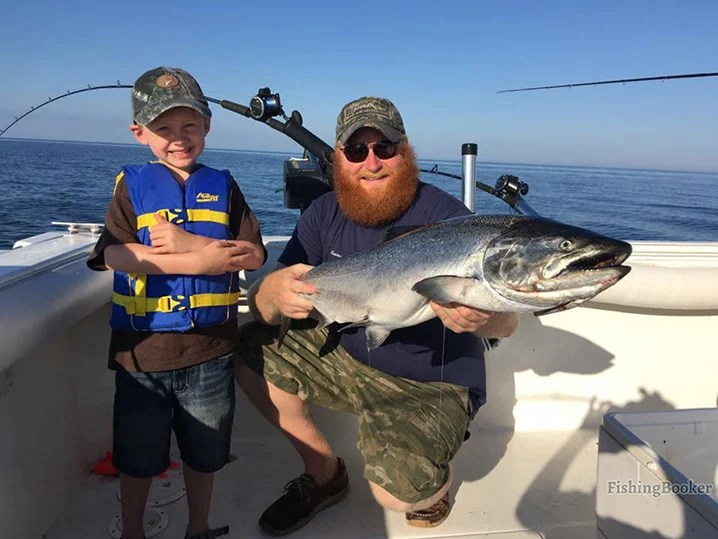 A dad and his son fishing on Lake Michigan and holding a big salmon.