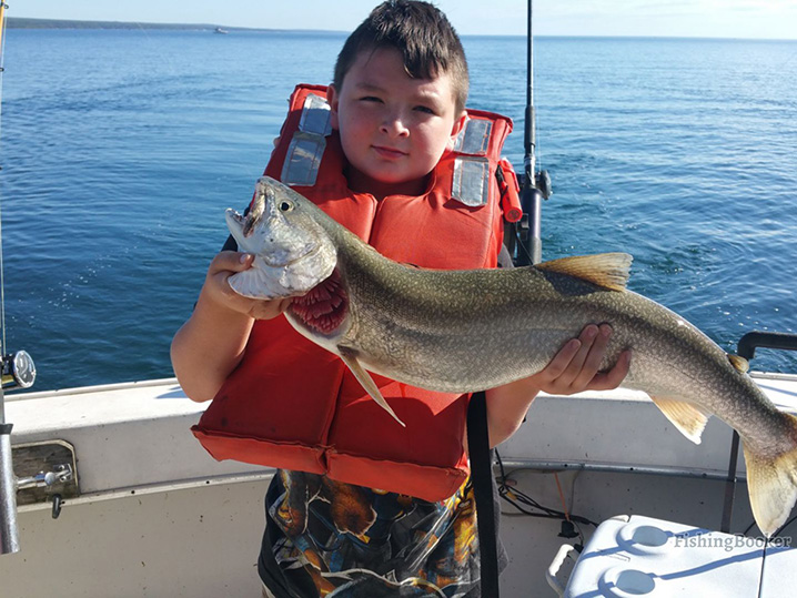 A young boy holding Walleye which he caught on a fishing trip with his family on the waters of the Lake of the Woods.
