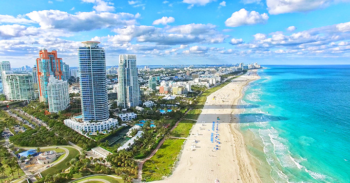 Miami waterfront with people sunbathing on sand beaches and swimming in the ocean