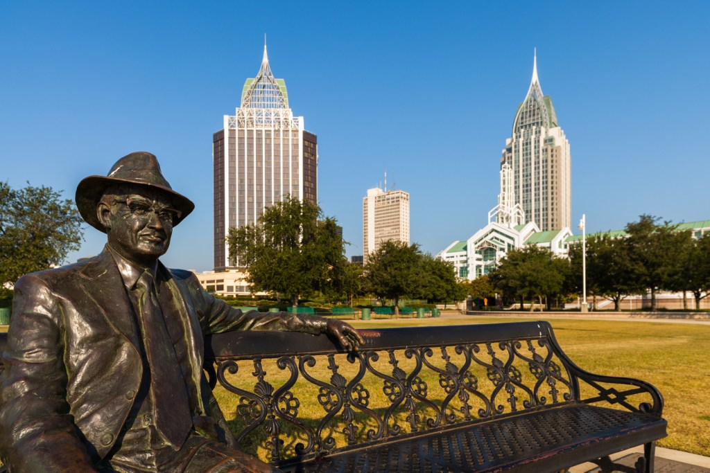 a statue with skyscrapers in the background in Mobile Alabama