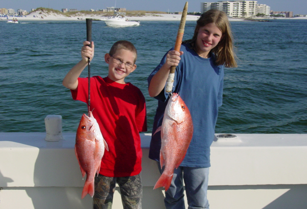 A boy and a girl on a charter fishing boat holding up the Red Snapper they caught
