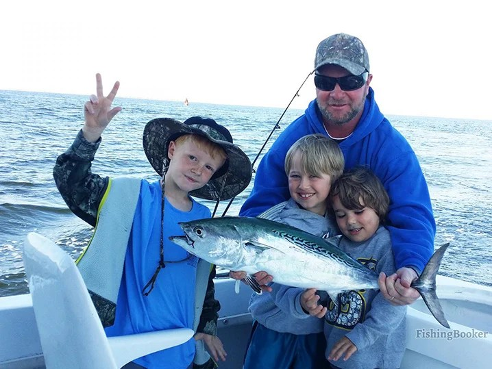 A dad and three kids on a family fishing trip in Nags Head holding a Bonito