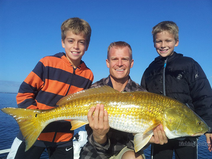 two boys and their dad holding big Redfish on a family fishing trip out of Orange Beach, AL.