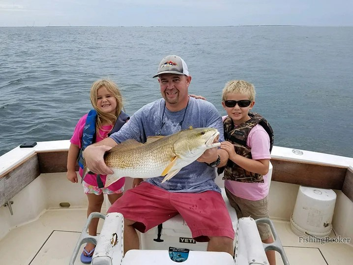 dad and his son and daughter holding a Redfish on a fishing charter in the Outer Banks sound.