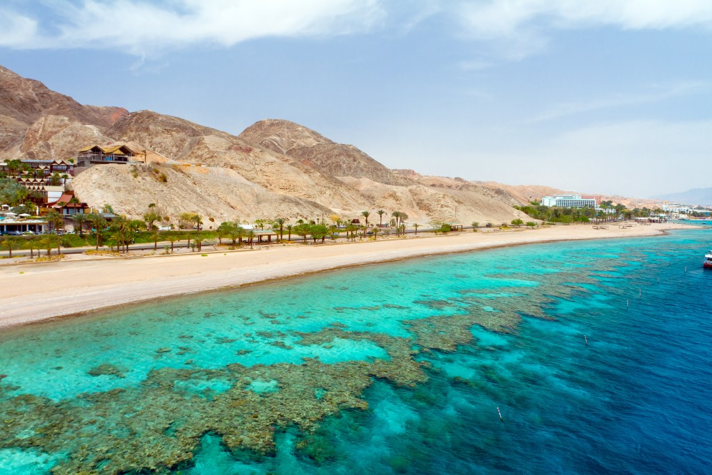 a view of the Red Sea Coral Reef and the shore dotted with tourist resorts