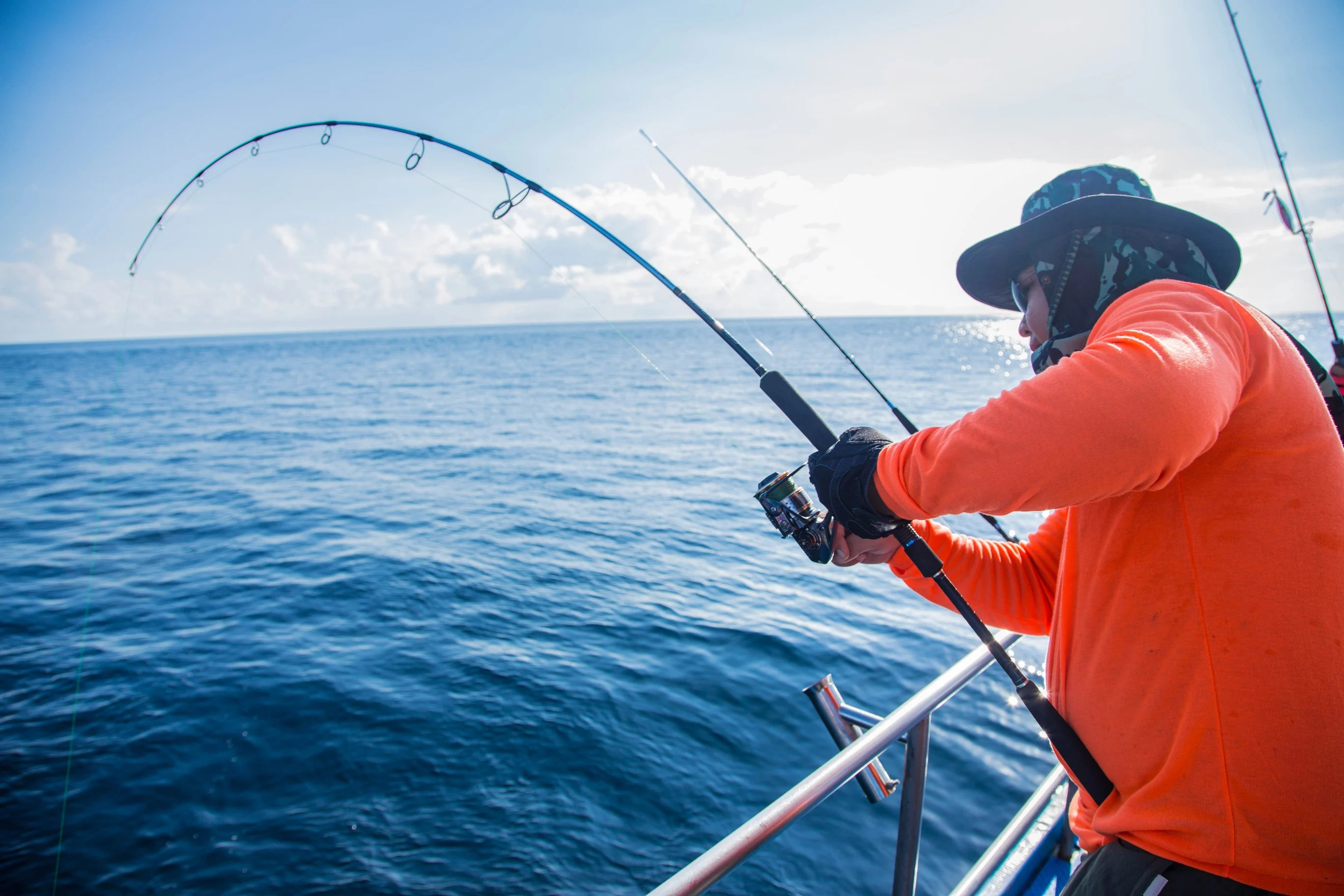 an angler holding a bent fishing rod on a fishing boat