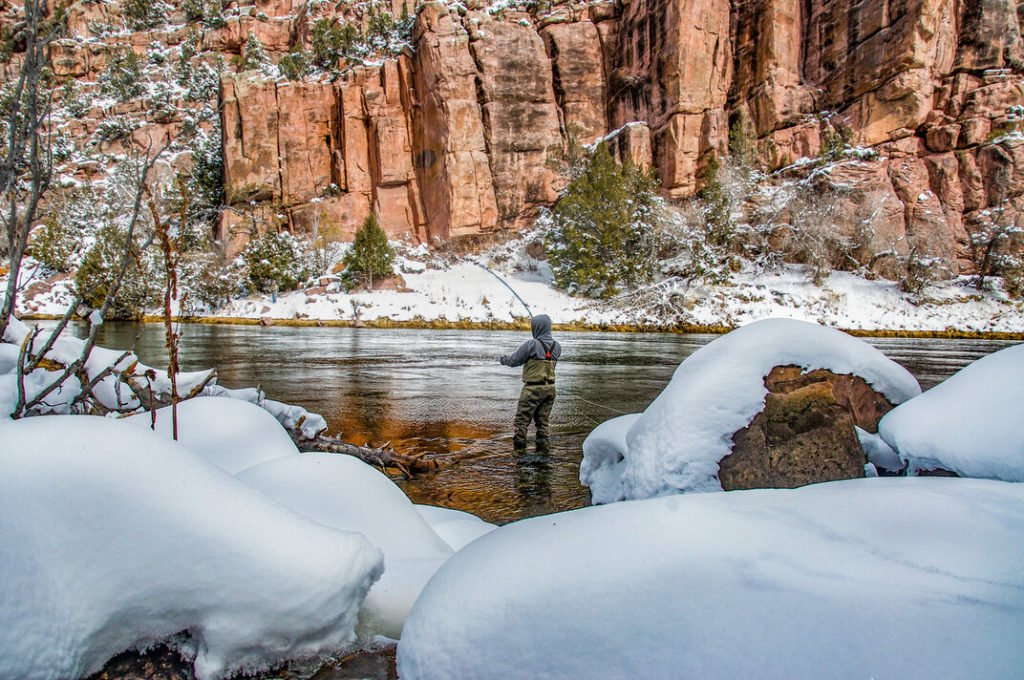 angler fishing in the river between snowy riverbanks