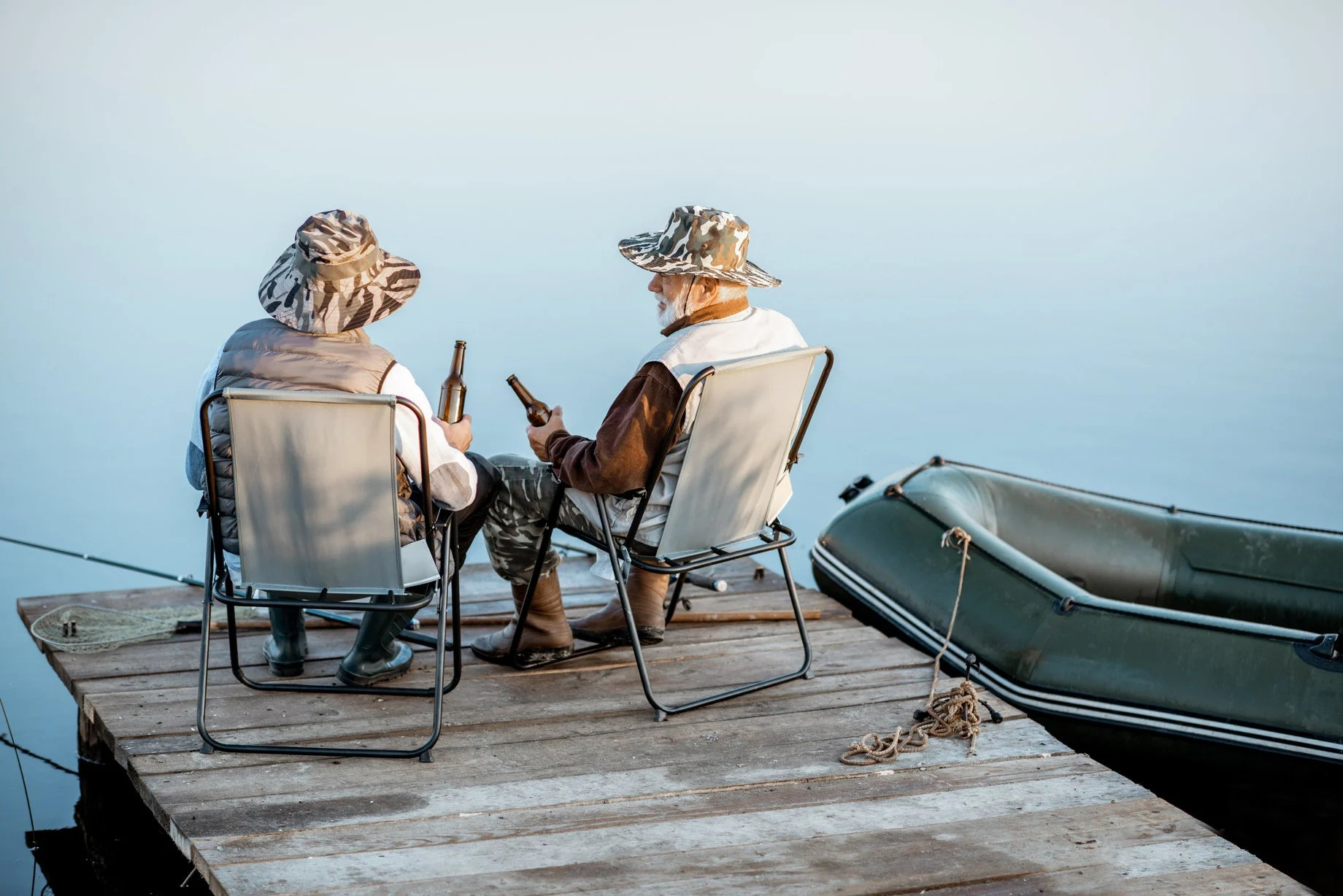 a couple of anglers sitting and drinking on a small fishing pier