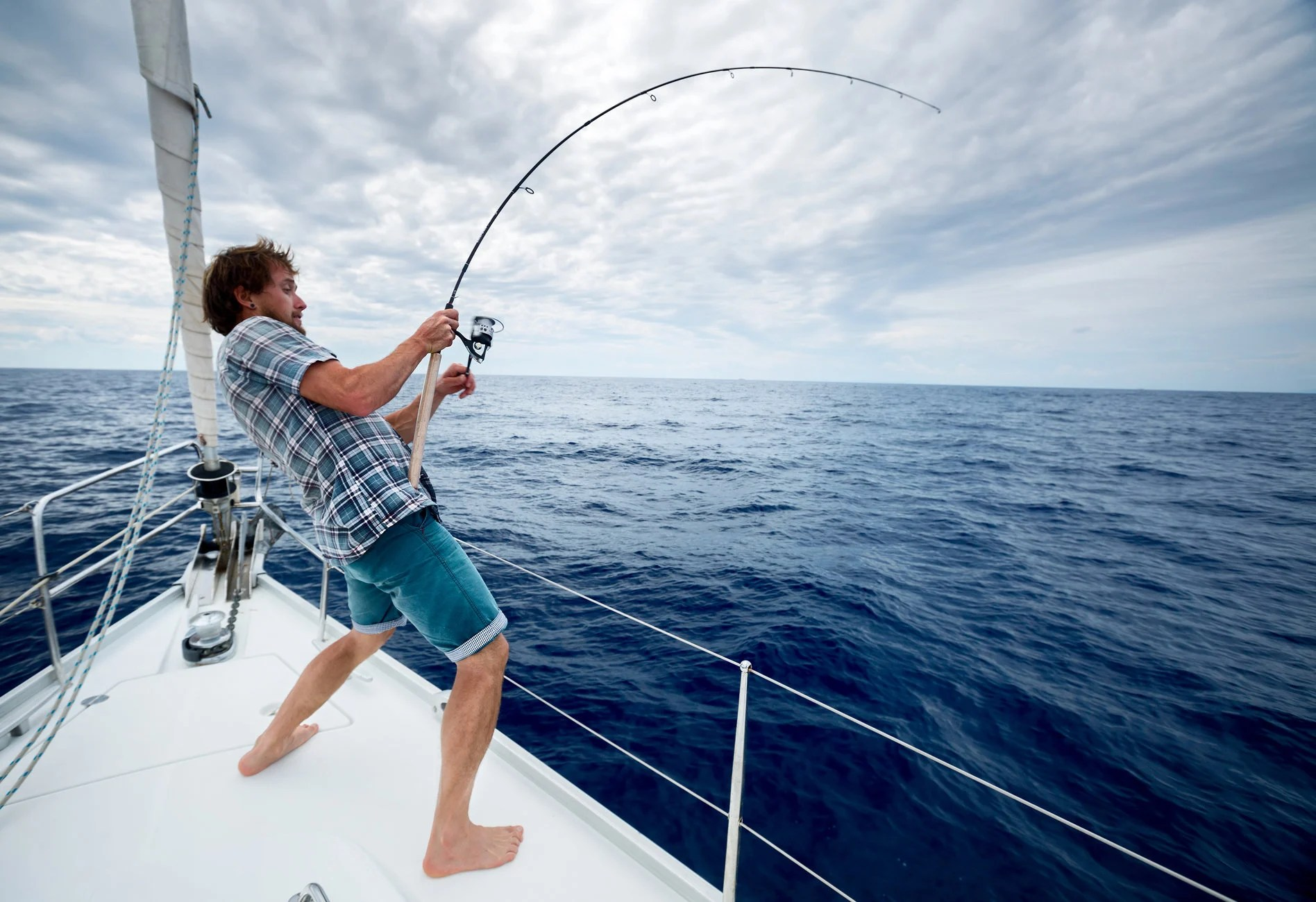an angler holding a bent fishing rod on a boat