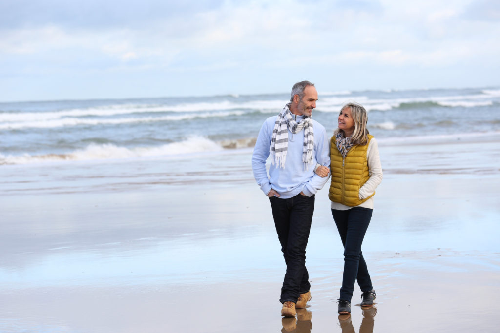 A senior couple walking together on a beach during a Valentine's Day date with waves behind them.