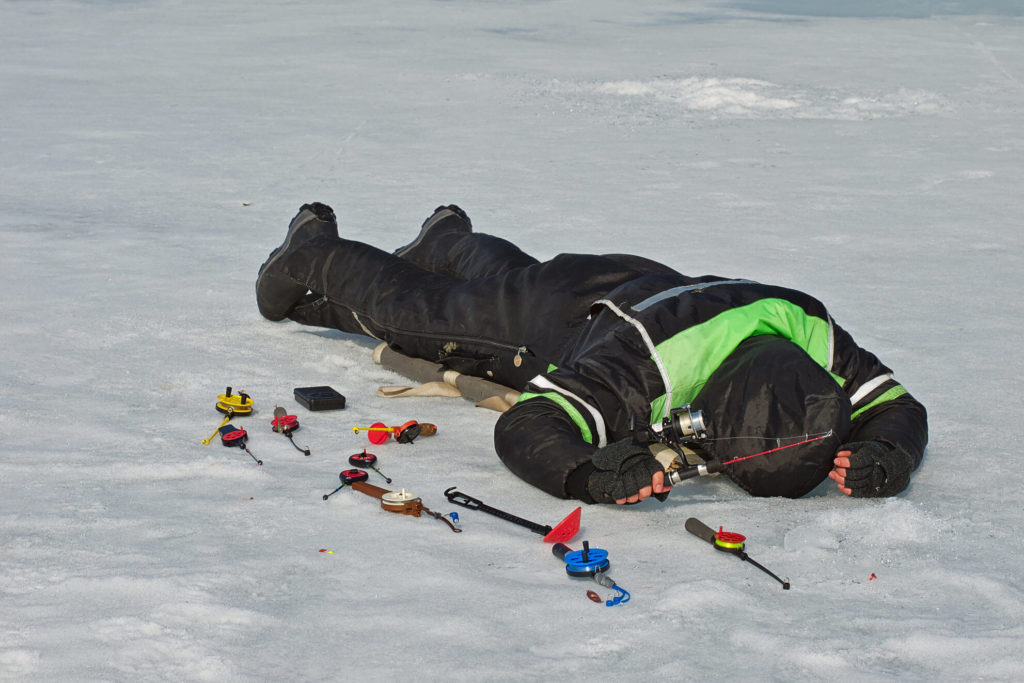 An ice angler looking down at a hole in the ice