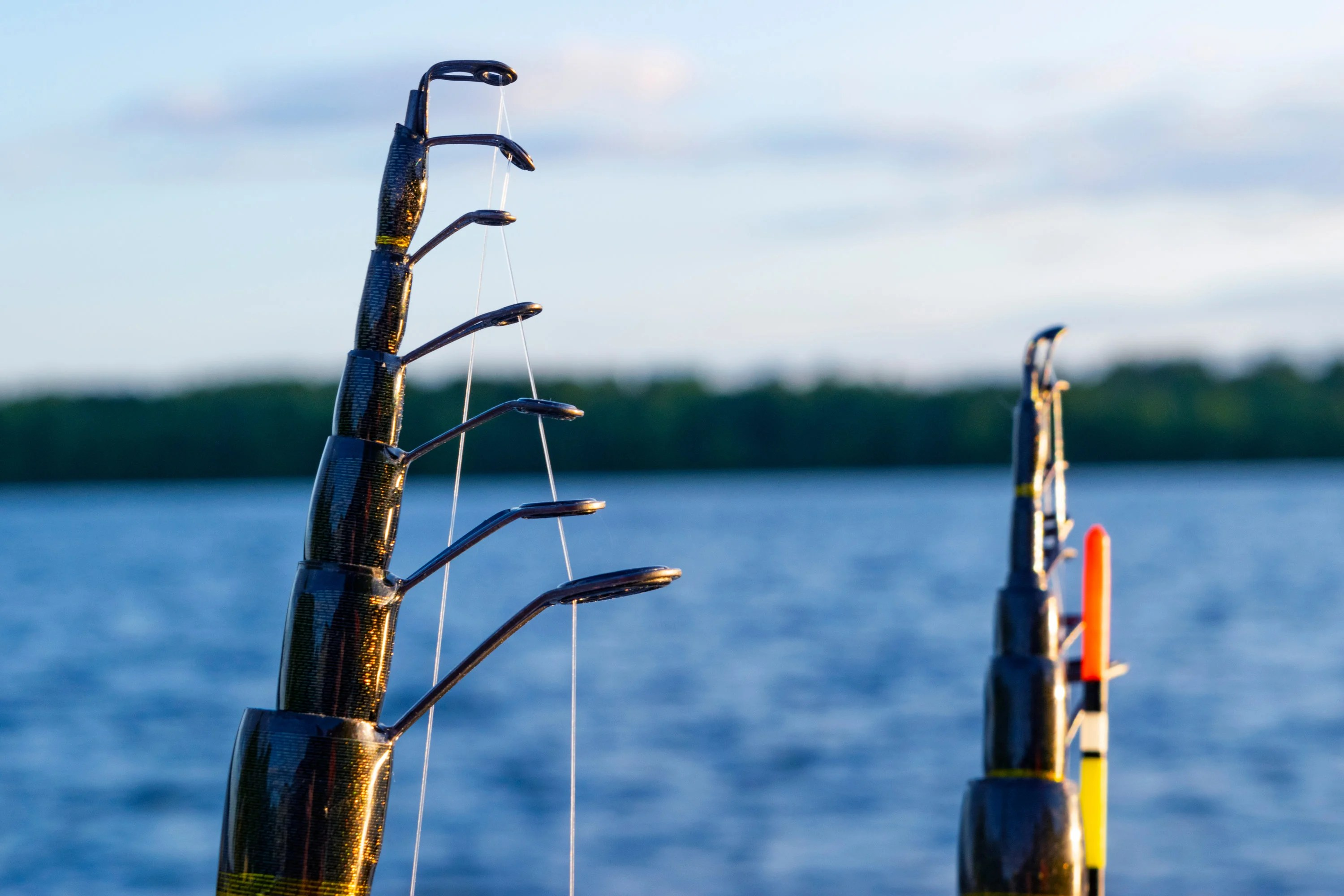 a closeup of guides on a telescopic fishing ord with blue waters in the background