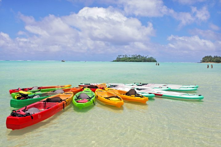 A group of kayaks and stand up paddle boards on the water