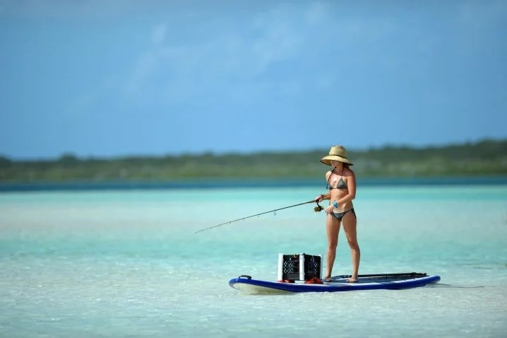 A woman in a bikini and a hat holding a fishing rod on a stand up paddle board