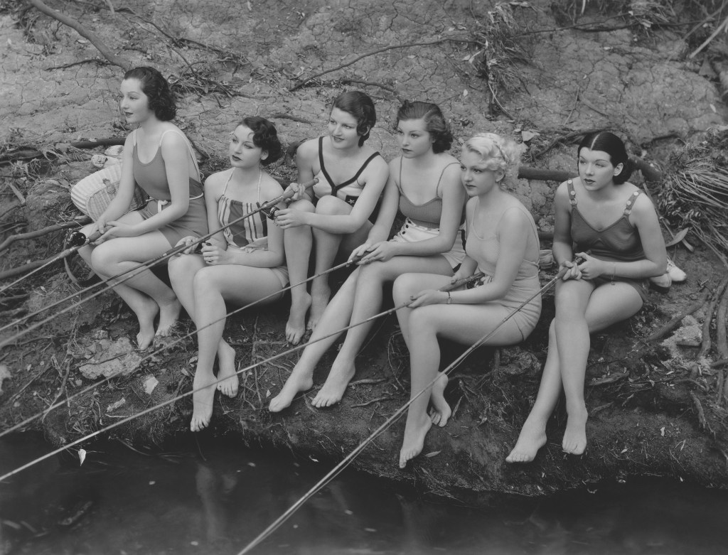 A vintage black and white photo of a group of women fishing.