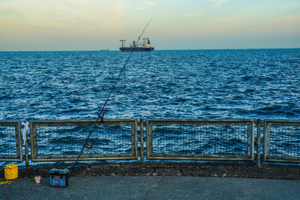 A view out to sea from a harbor wall, with a fishing rod leaned against a rail and a cargo ship on the horizon