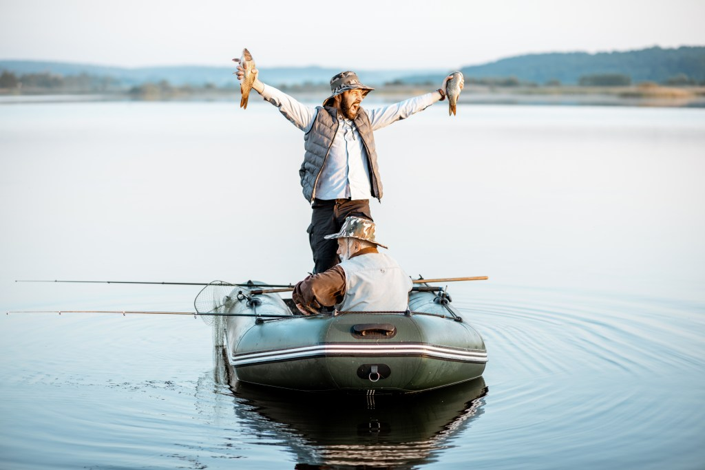 Man standing on a boat in a lake happy and holding fish