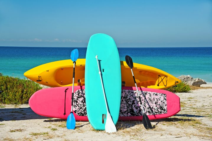 A turquoise stand up paddle board leaning on a pink SUP board and a yellow kayak with the sea in the background