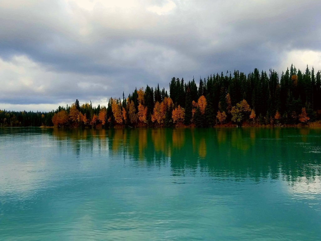 View of clear Kasilof River with a forest and cloudy skies