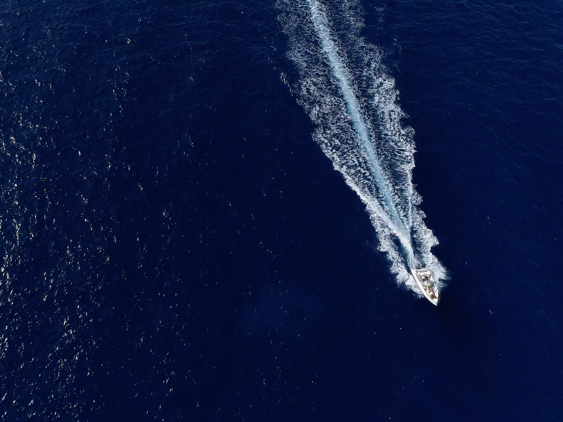An aerial photo of a sportfishing yacht in the ocean