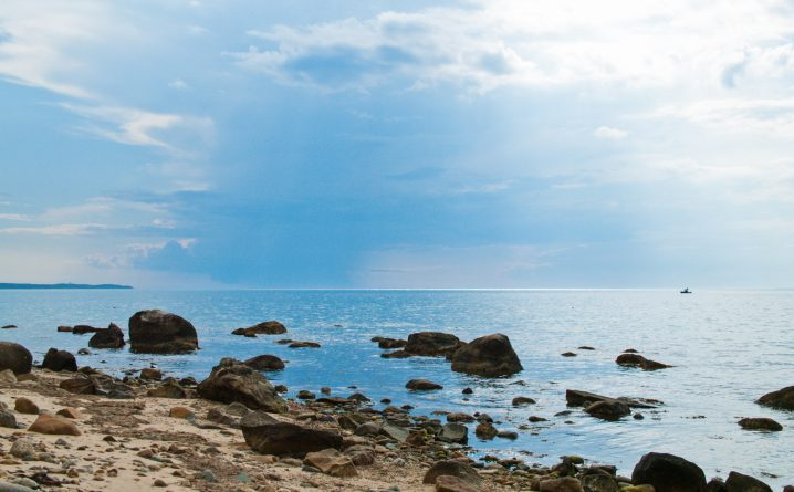 A calm coastline with a rocky beach and boulders sticking out of the water
