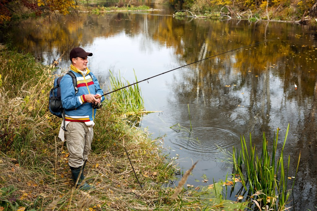 A solo angler fishing from shore in autumn