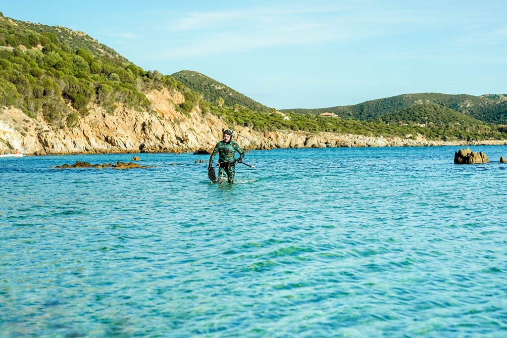 A man emerges from the sea with spearfishing gear on the Croatian coast