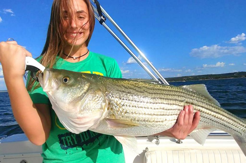 a smiling angler holding a striped bass on a boat