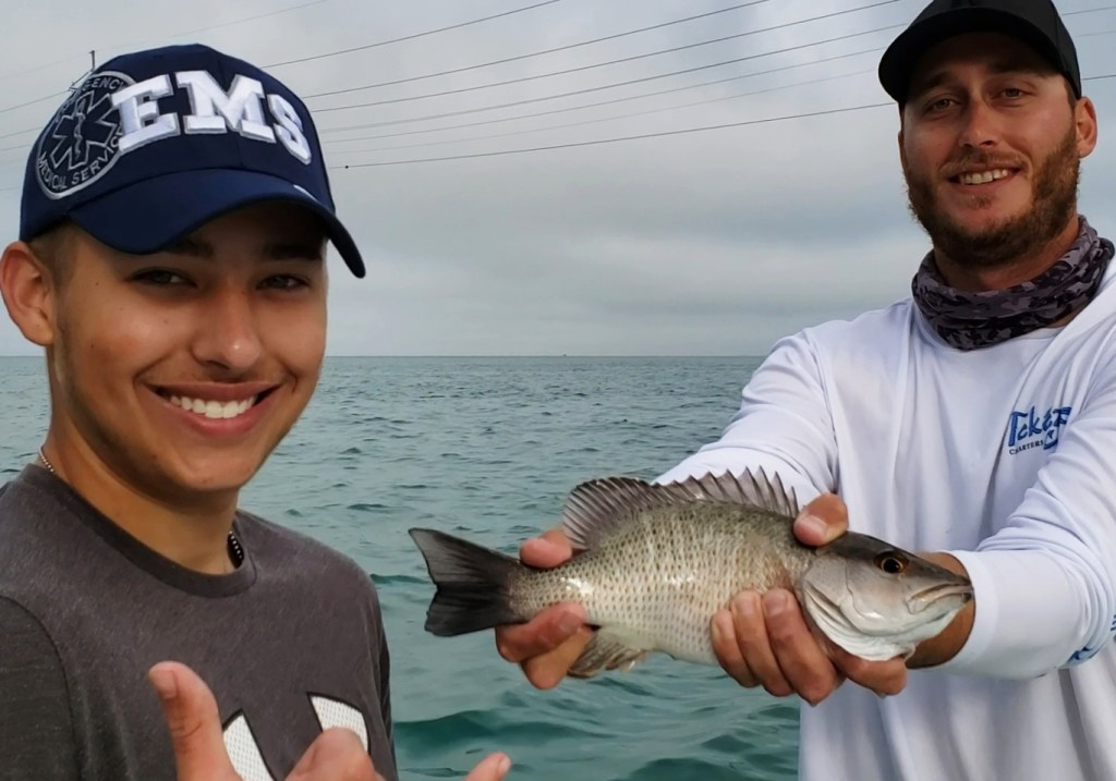 Two happy people holding a snapper fish