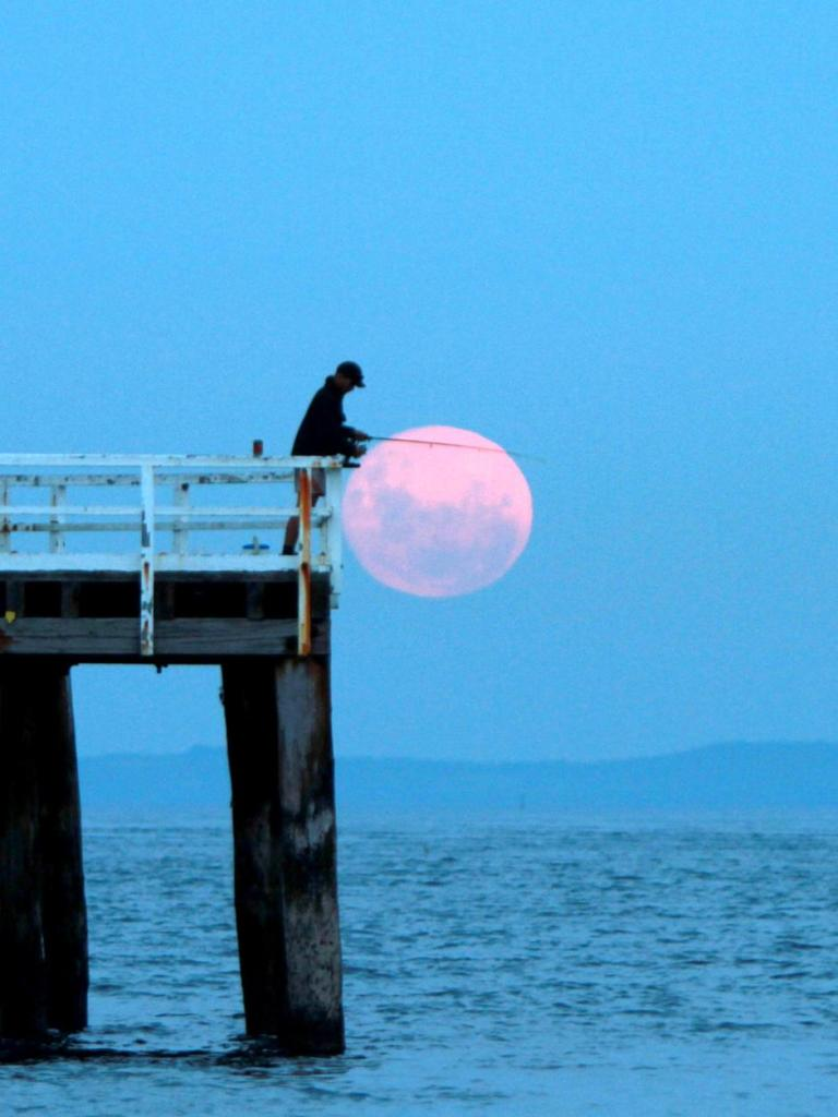 The full moon rises behind an angler fishing from a pier