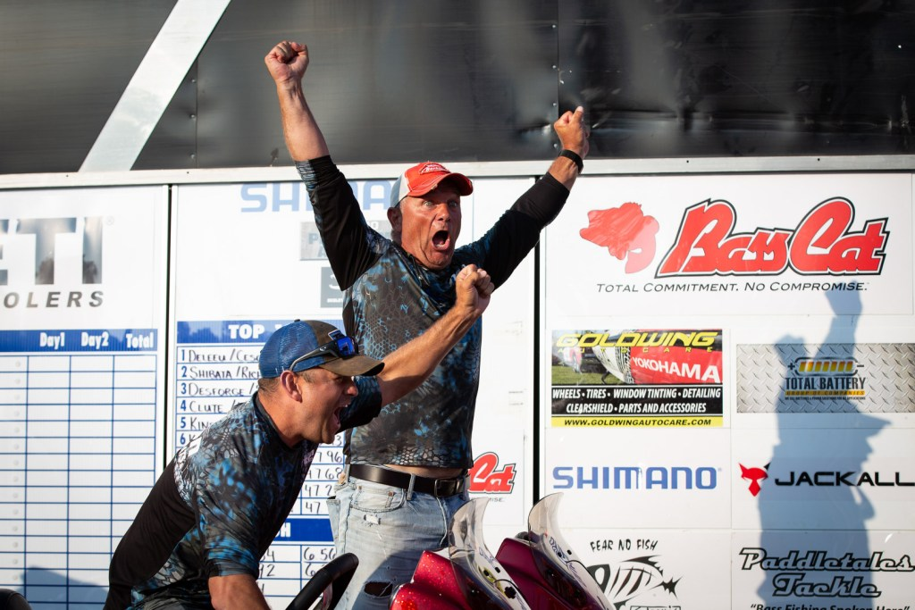 Two men celebrate winning a boat at a bass fishing tournament in Kingston, Ontario