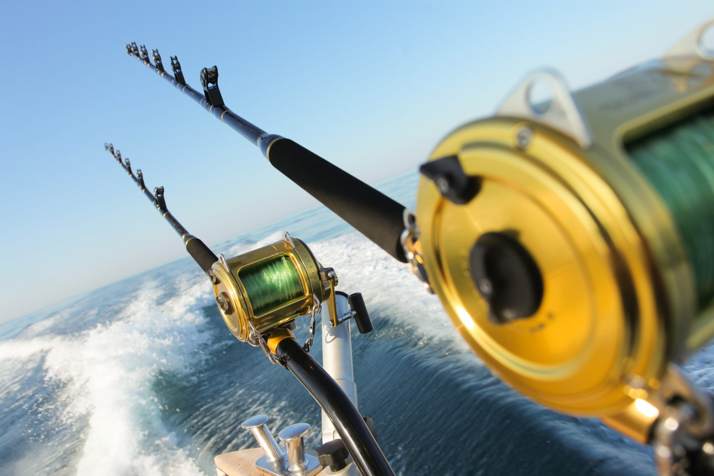 trolling rods on a moving fishing boat with the water in the background