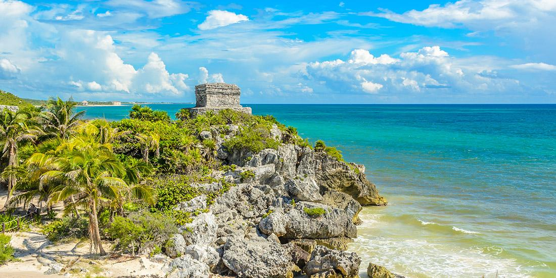 a view of the ancient ruins of Tulum, with the Mexican Caribbean in the background