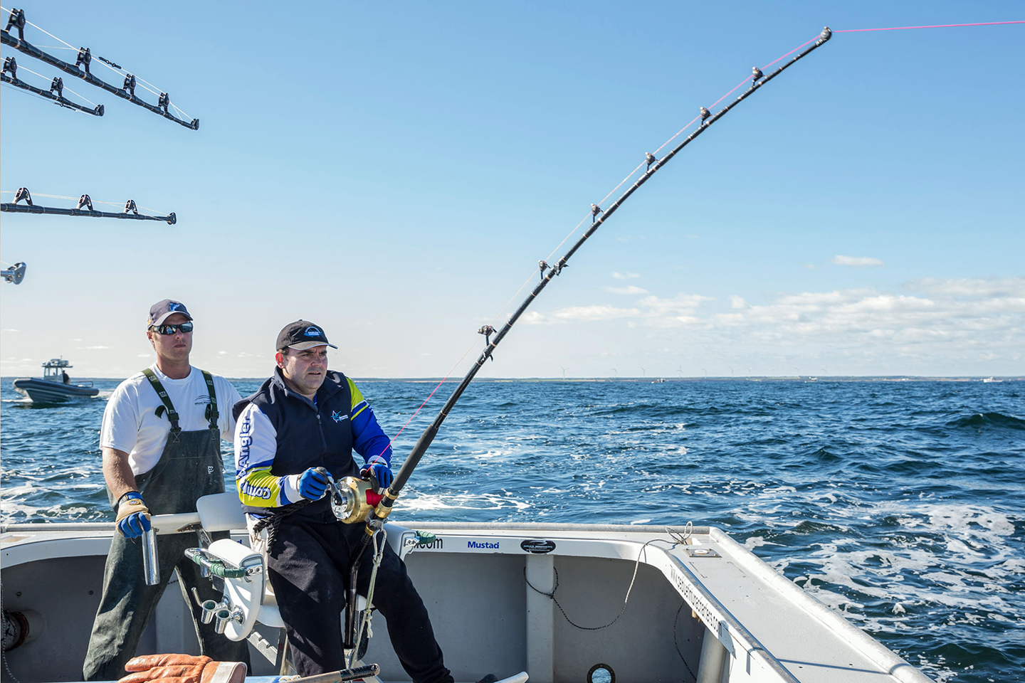 An anglers fighting a huge fish with a fighting chair and heavy tackle, with a crew member helping them behind