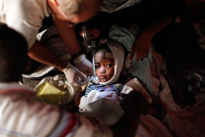 Медики помогают раненому ребенку после землетрясения в Порт-о-Пренс 13 января.