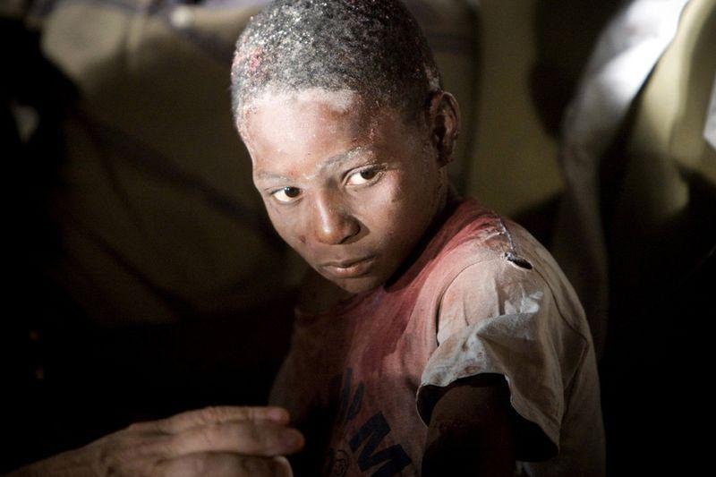 Медики помогают раненому мальчику в отеле Вилла Креоле в Порт-о-Пренс после землетрясения в 7.0 баллов.