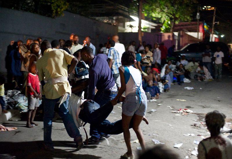 Оставшиеся без крова люди выносят раненого из больницы, после начала третьего толчка 13 января в Порт-о-Пренс.