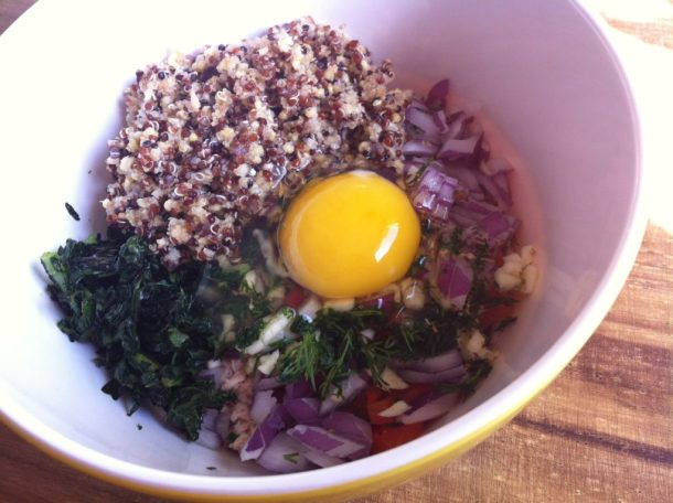A bowl filled with ingredients to make a tuna burger. The ingredients include cooked quinoa, cooked kale, red onion, roasted red pepper, and egg.