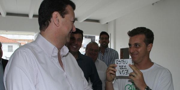 22dez2012---sem-voz-o-apresentador-luciano-huck-precisou-apelar-para-uma-plaquinha-para-se-comunicar-com-o-prefeito-de-sao-paulo-gilberto-kassab-durante-visita-oficial-a-1356185026552_956x500