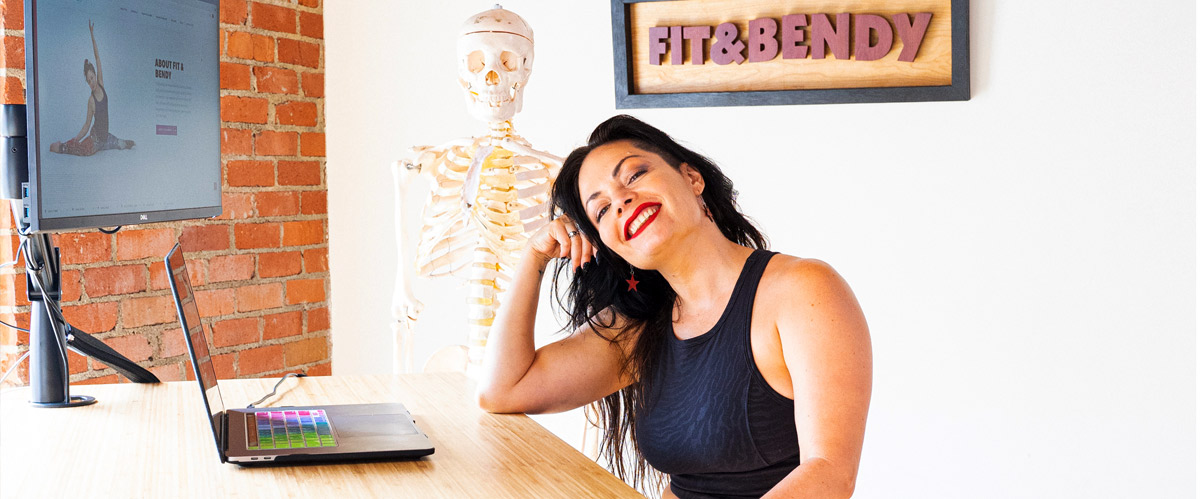Kristina Nekyia sitting in front of a computer with an anatomical skeleton