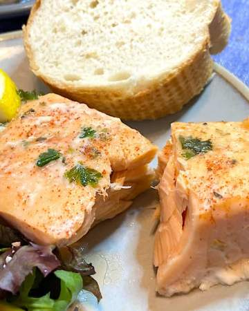 juicy oven baked salmon with salad and bread on plate